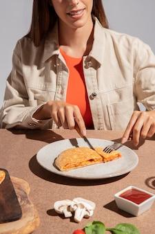 Молодая женщина, наслаждаясь вкусной пиццей кальцоне Premium Фотографии