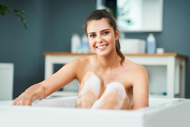 Молодая женщина, наслаждаясь и расслабляясь в ванне