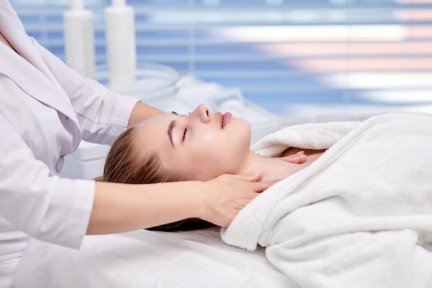 노화 방지 얼굴 마사지를 즐기는 젊은 여성 예쁜 아가씨가 웰빙 센터에서 전문적인 피부 관리를 받고 있습니다.