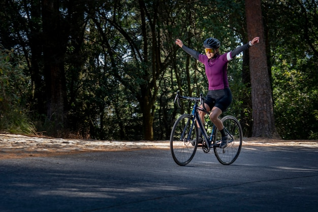Young woman enjoying a bike ride outdoors in the middle of the forest