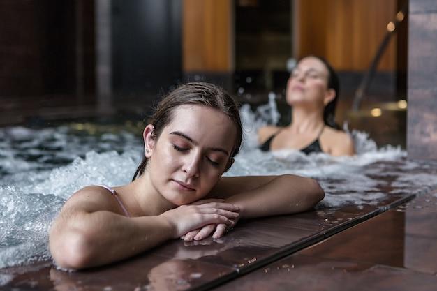 Молодая женщина, наслаждаясь пузырящейся водой в спа-центре