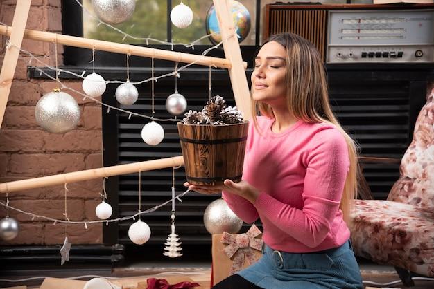 집에서 솔방울 양동이를 즐기는 젊은 여성.