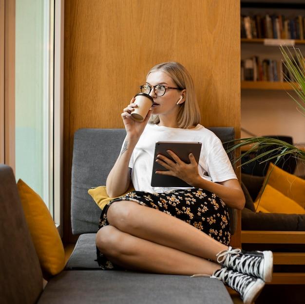 Giovane donna che gode del caffè in biblioteca
