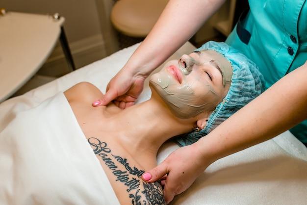 Молодая женщина, наслаждаясь массажем лица в спа-салоне. массаж лица ..