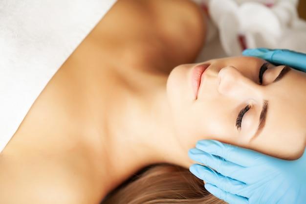 Young woman enjoying of facial massage in spa salon.