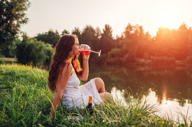 Young woman enjoying glass of wine on river bank at sunset.