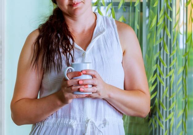 젊은 여성이 그녀의 모닝 커피 또는 차를 즐기고, 아름다운 낭만적 인 찾고