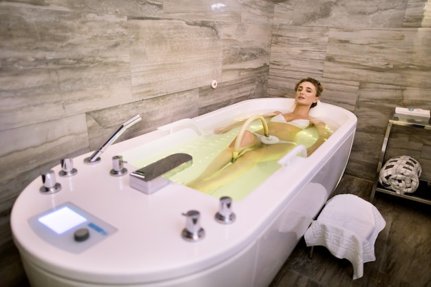 Young woman enjoying hydromassage in whirl pool bath with green lights. relaxed woman getting hydromassage in professional spa center