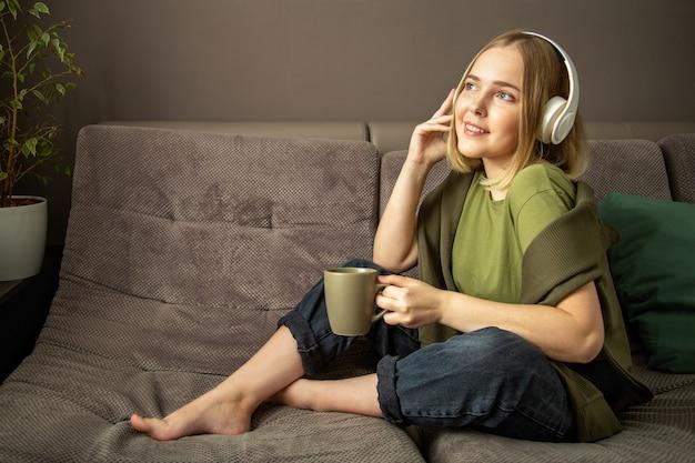 イヤホンで歌を聞くのを楽しむ若い女性。幸せなミレニアル世代の 10 代の少女は、お茶を飲み、リビング ルームのソファのイヤホンで音楽を聴きながらリラックスします。かわいい金髪の 10 代の少女の笑顔は家で休む。
