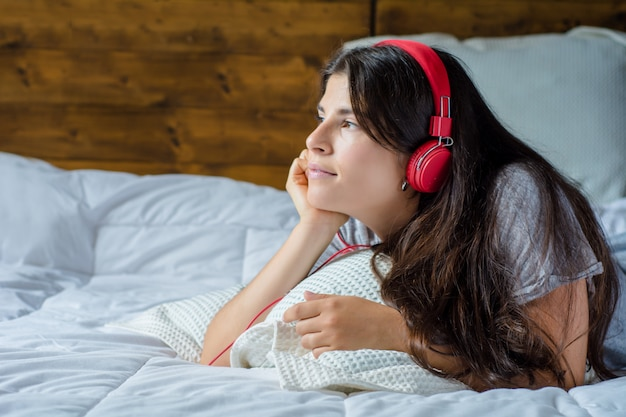 Young woman enjoying music on bed.