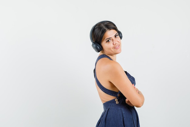 ドレスを着てヘッドフォンで音楽を楽しんで、陽気に見える若い女性。 。