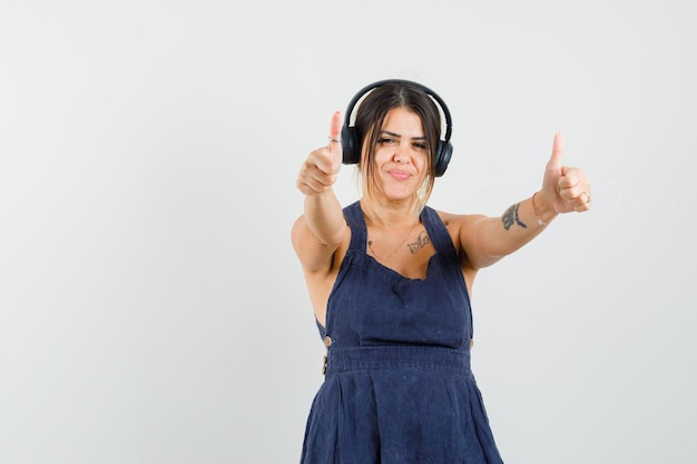 Young woman enjoying music with headphones, showing thumbs up in dress