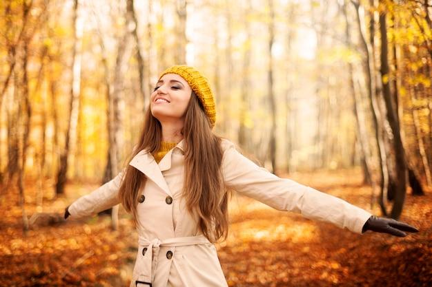 秋に自然を楽しむ若い女性