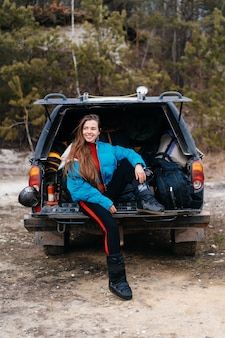 Young woman enjoying nature while sitting in the car trunk