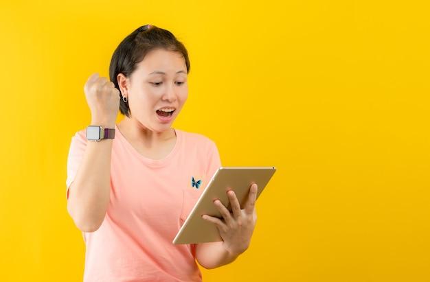 黄色の背景に対して自宅で楽しくオンラインショッピングを楽しんでいる若い女性