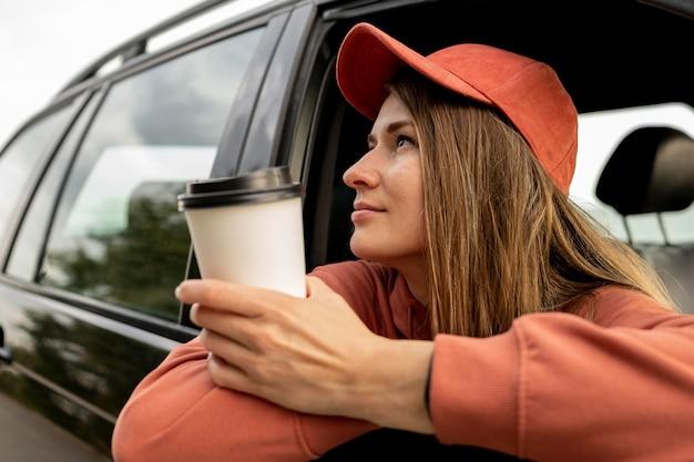 Giovane donna che gode del viaggio su strada