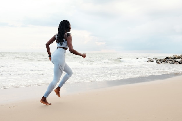 夏の日の朝のビーチでのランニングを楽しんでいる若い女性