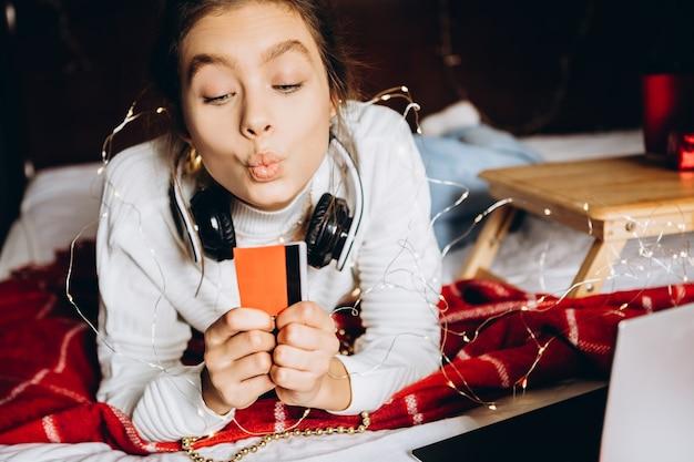 Молодая женщина, наслаждаясь покупками в интернете на рождество