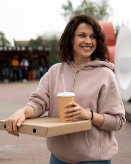 Молодая женщина, наслаждаясь вкусной уличной едой