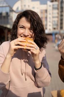 Молодая женщина, наслаждаясь уличной едой на открытом воздухе