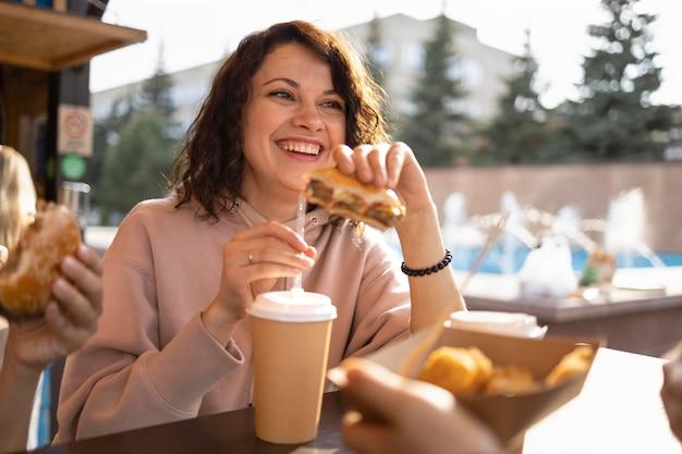 Молодая женщина, наслаждающаяся уличной едой