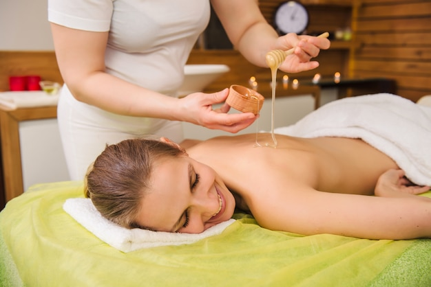 Молодая женщина, наслаждаясь спа-процедуры с медом