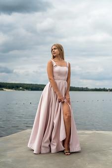 Young woman enjoying summer time posing alone in cute ping dress near lake, lifestyle