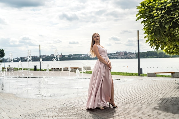 湖の近くのかわいいpingドレス、ライフスタイルで一人でポーズをとって夏の時間を楽しんでいる若い女性