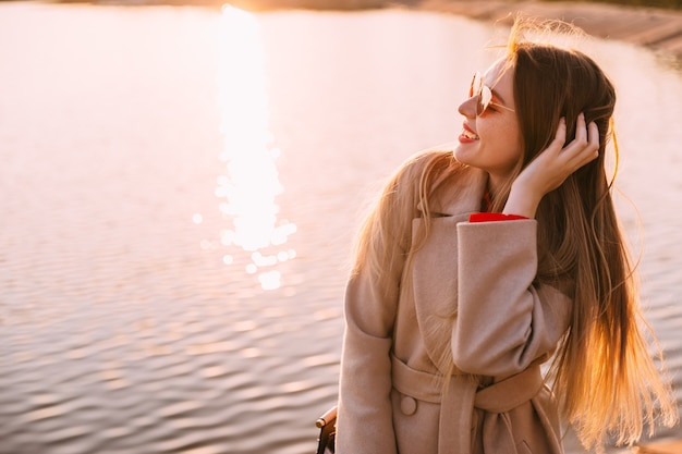 夕日を楽しむ若い女性。美しい少女の肖像画、風が舞う髪。旅行、ライフスタイル、冒険、コンセプト。