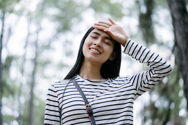 Молодая женщина, наслаждаясь свежим воздухом в сосновом лесу, отдых в природе счастливой концепции.