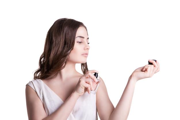 Молодая женщина, наслаждаясь запахом духов на ее запястье