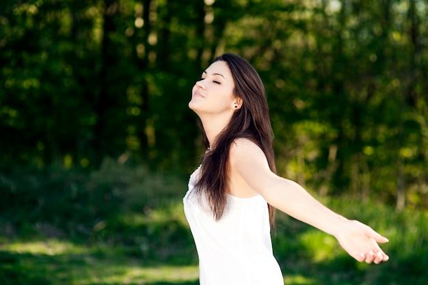 公園で夏を楽しんでいる若い女性