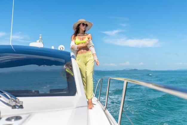 海のヨットで晴れた日を楽しんでいる若い女性