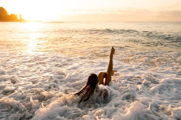 ビーチで時間を楽しんでいる若い女性