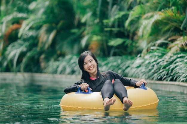 怠惰な川のプールでチューブを楽しむ若い女性