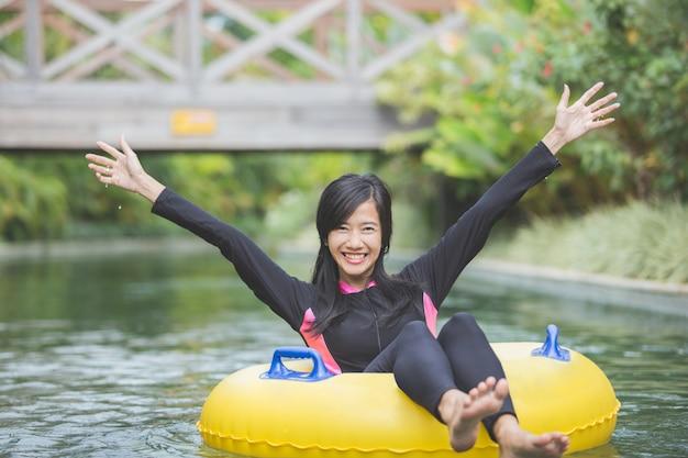 Young woman enjoying tubing at lazy river pool