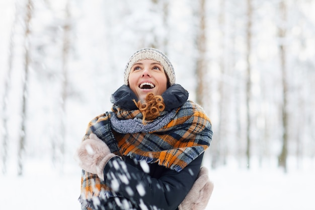 Молодая женщина, наслаждаясь зимой