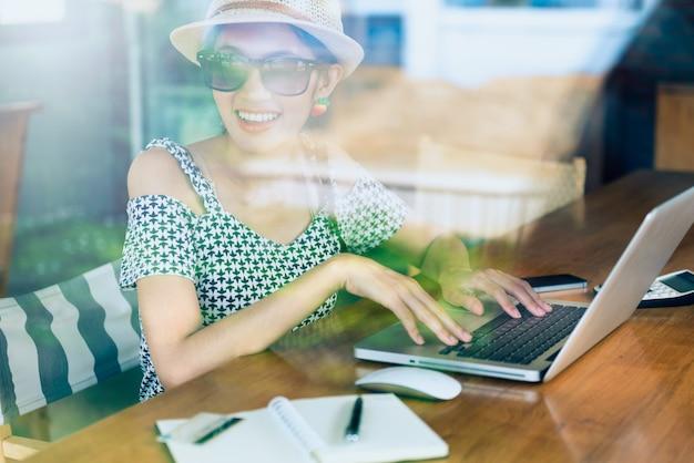 Молодая женщина, наслаждаясь работы сидя возле окна в кафе с отражением окна