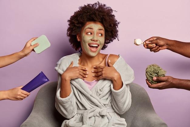 若い女性はバスローブに座って自宅で美容スパを楽しんでいます