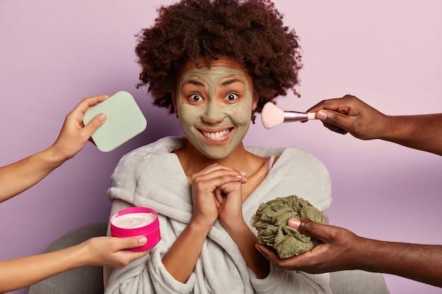 젊은 여자 목욕 가운에 집 siting에서 뷰티 스파를 즐긴다