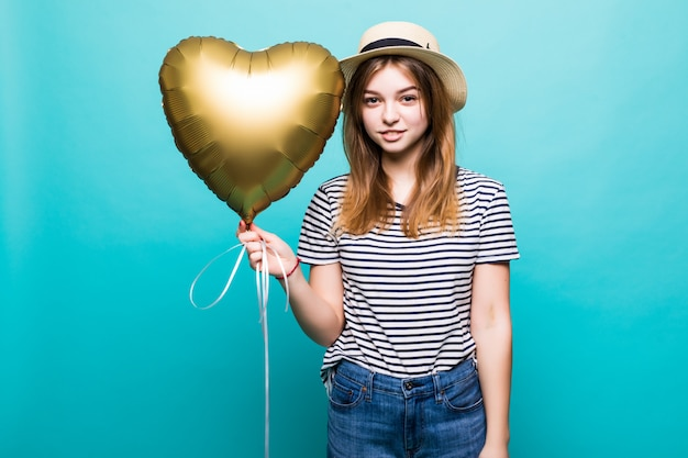 Young woman enjoys festive occasion holding metallic balloon