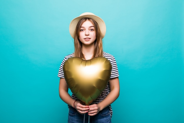 Young woman enjoys festive occasion holding metallic balloon