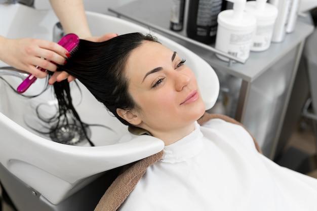 若い女性は、ビューティーサロンでヘアケアを楽しんでいます。美容師はクライアントの女の子の髪を洗い、保湿オイルマスクを塗り、櫛で髪をとかします。美容院でのヘアケアのプロセス
