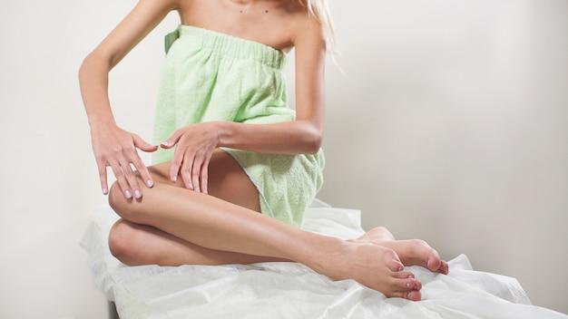 Молодая женщина наслаждается своими ухоженными гладкими ногами после эпиляции