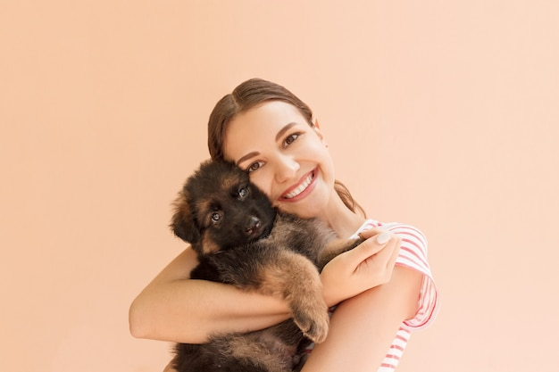 Young woman enjoys hugging a small cute puppy