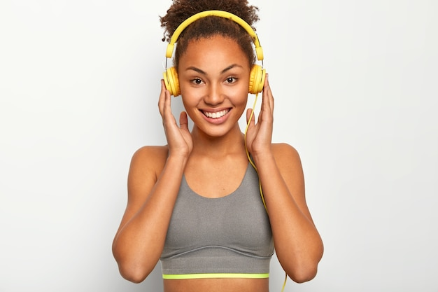 젊은 여성은 개인적인 동기로 음악을 즐기고, 헤드폰에 양손을 대고, 즐겁게 미소를 짓고, 회색 스포츠 브래지어를 착용합니다.