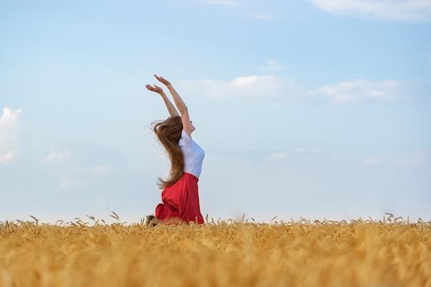젊은 여자는 태양을 즐기고 좋은 날씨는 밀밭의 중간에 있습니다. 기쁨을 위해 점프