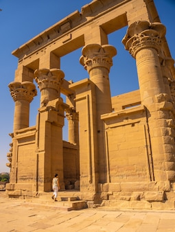A young woman entering the temple of philae with its beautiful columns, a greco-roman construction, a temple dedicated to isis, goddess of love. aswan. egyptian
