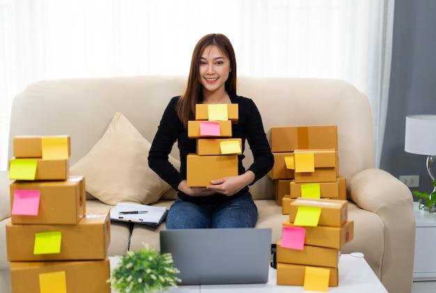Молодая женщина-предприниматель готовит посылку в домашнем офисе