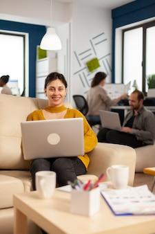 ビジネスの途中でソファに座っている若い女性起業家は、ラップトップを持って笑顔のカメラを見てオフィスを起動します